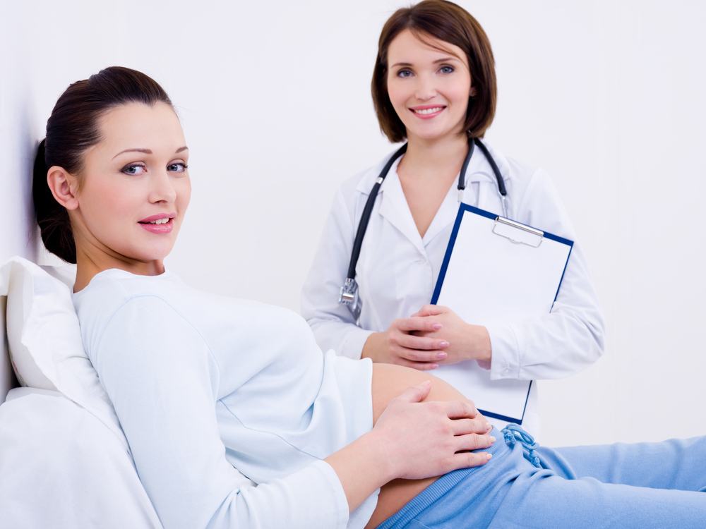 Beautiful smiling pregnant woman with the doctor at hospital for spotting checkup